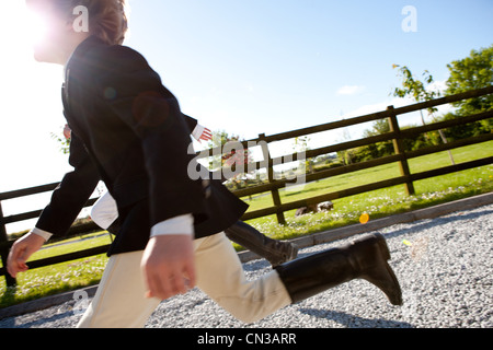 Boys running in horse riding clothes - Stock Photo