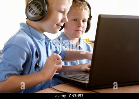 Two school boys wearing headphones,  looking at computer screen - Stock Photo