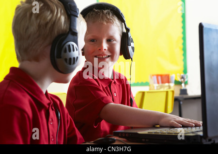 School boys wearing headphones and looking at computer in classroom - Stock Photo