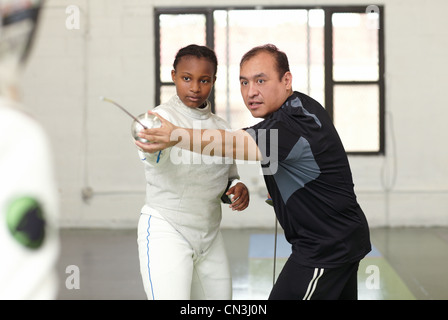 Fencing tutor assisting female student - Stock Photo
