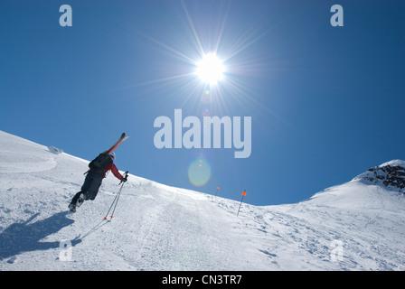 Skier walking up Blackcomb ski hill, heading for backcountry, Garibaldi Provincial Park, Whistler, British Columbia - Stock Photo