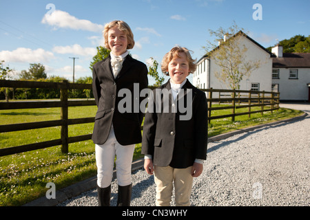 Portrait of boys wearing horse riding clothes - Stock Photo