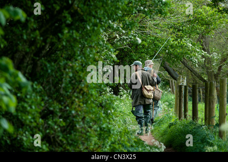 Two people on a path going fishing - Stock Photo