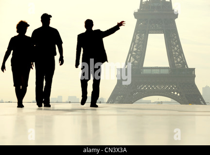 Silhouette of people walking in front of the Eiffel Tower - Stock Photo