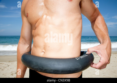 Man on beach pinching tyre around waist - Stock Photo