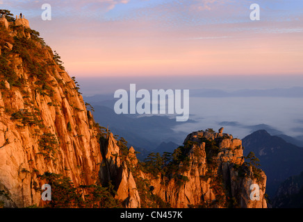 Red sun on Lion Peak and Stone Monkey watching the Sea Peak at first light with fog in valley at Huangshan Yellow - Stock Photo