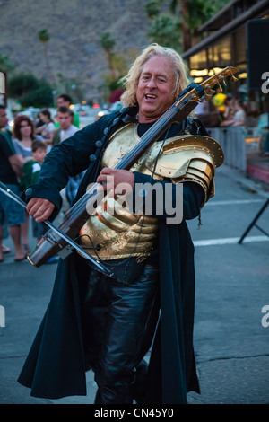 A 45-50 year old street musician wears gold armor and plays an electronic string instrument during a street fair - Stock Photo