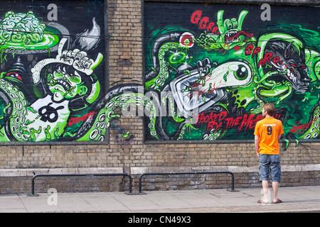 United Kingdom, London, Hackney, Shoreditch, passer by looking at a graffiti - Stock Photo
