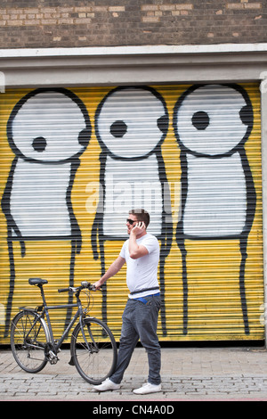 United Kingdom, London, Hackney, Shoreditch, Curtain Road, Mutate Britain, cyclist in front of a graffiti by Stik - Stock Photo
