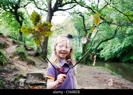 Girl holding an oak branch in a woodland - Stock Photo