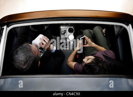 Businessmen and women haring car to work, overhead view - Stock Photo