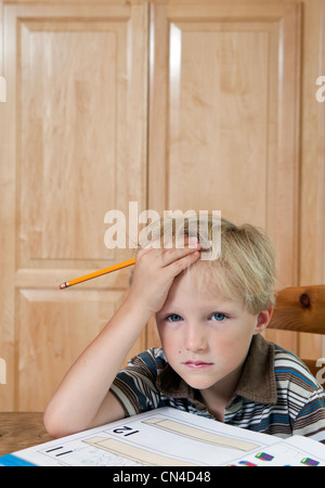 Boy looking confused over homework, portrait - Stock Photo