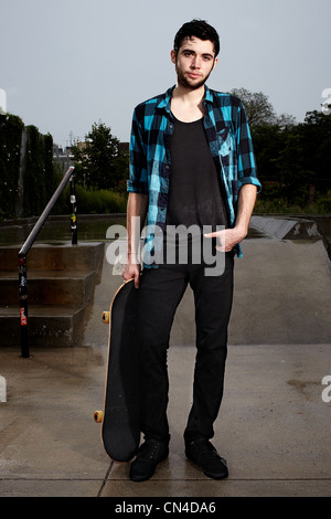 Young skateboarder in skate park, portrait - Stock Photo