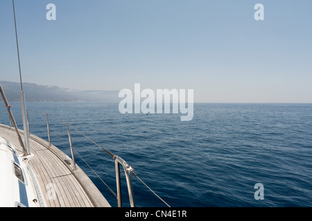 View of the side of a yacht and the Sardinian coast - Stock Photo