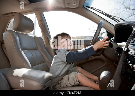 Little boy pretending to drive car - Stock Photo