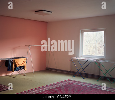 Drying laundry in empty room - Stock Photo