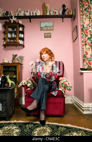 Senior woman in living room with wine and cigarette, smiling - Stock Photo