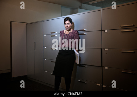 Office worker holding file behind back by filing cabinets - Stock Photo
