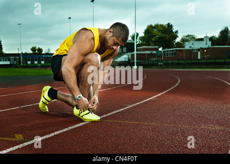 Sprinter tying shoelace on race track