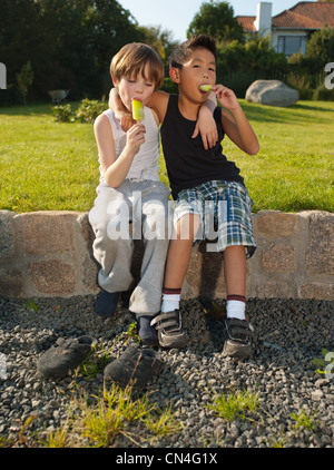 Boys sitting on wall and enjoying ice loliies, portrait - Stock Photo