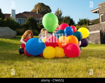 Girls behind multicoloured balloons - Stock Photo