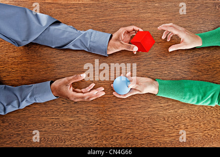 People exchanging colourful shapes - Stock Photo