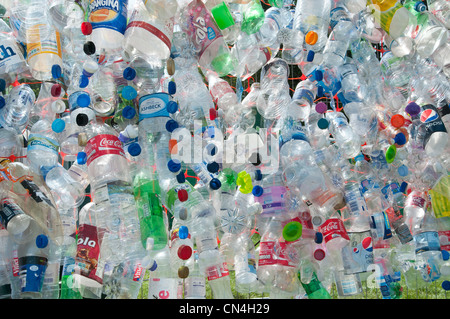 Discarded plastic bottles attached to a wire mesh fence highlight the need for more recycling of precious materials - Stock Photo