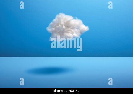 Cotton ball cloud against blue backdrop - Stock Photo