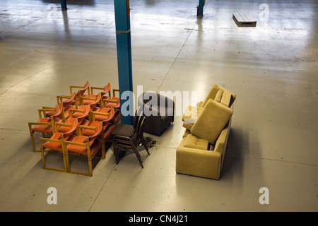 Chairs stacked in an empty warehouse - Stock Photo