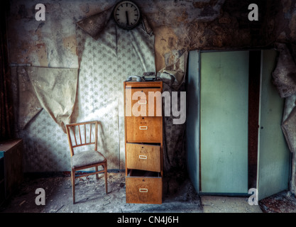 Abandoned building with chair and filing cabinet - Stock Photo
