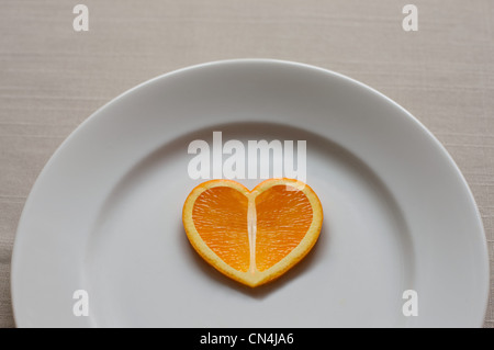 Orange slice in the shape of a heart - Stock Photo