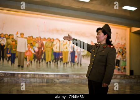 North Korea, Pyongyang, Victorious Fatherland Liberation war Museum, female soldier guide describing a frescoe showing - Stock Photo