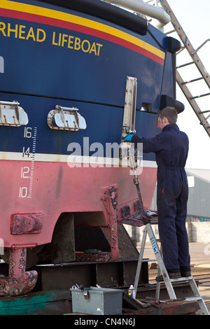 Engineers working on Peterhead Lifeboat. Fraserburgh ship repair yards. Scotland UK - Stock Photo