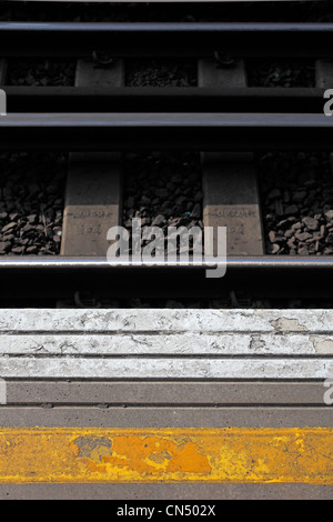 Yellow and white paint on platform of London train station and tracks and stones in background - Stock Photo