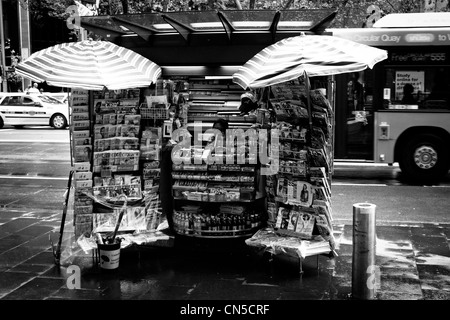 A small stall on the side of the road selling newspapers and other items during a rainy day in the city - Stock Photo
