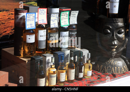 Bottles of Scottish malt whisky in a window display for sale in a shop in Peebles in the Scottish Borders - Stock Photo