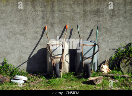 Two wheel barrows leaning up against a wall outside in a garden - Stock Photo