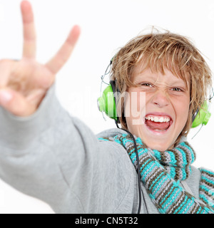 happy kid doing v sign and listening to music wearing headphones. - Stock Photo