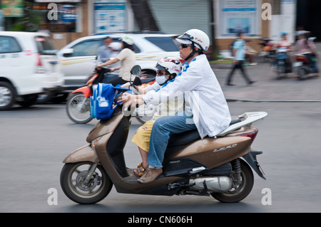 Schoolboy travelling home by motorbike, Saigon, Vietnam - Stock Photo