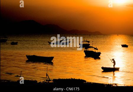 fisherman poles sampan to beach at sunset at harbor in South China Sea New Territories Hong Kong China - Stock Photo