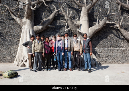 Punjabi college students pose with a western tourist in front of concrete trees in the rock gardens of Chandigarh - Stock Photo