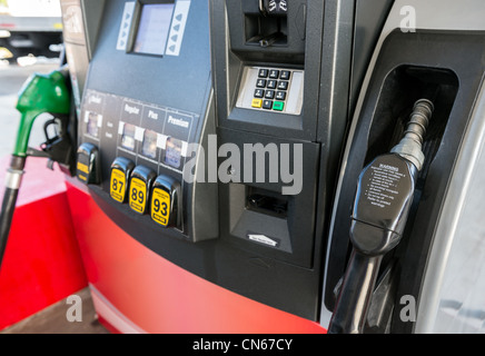 Gas pump close up with nozzle in foreground. - Stock Photo