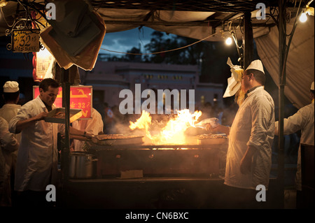 Cooks in a food stall of the Djemaa El Fna Square of Marakech, Morocco. - Stock Photo
