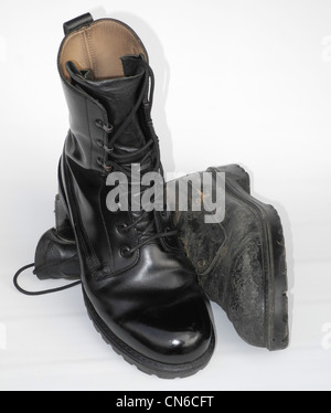 A well cared for military boot - army polished - with a well worn one - Stock Photo