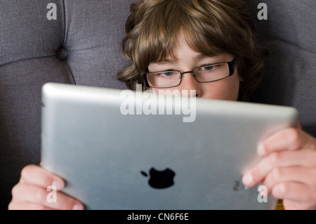 A young boy playing on an iPad - Stock Photo