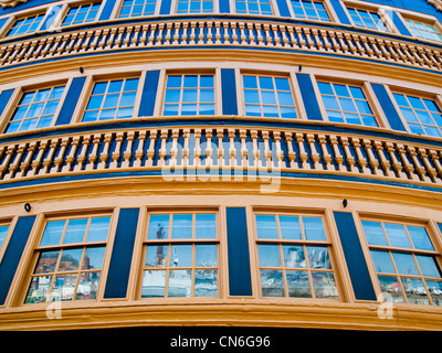 The stern windows of HMS Victory in Portsmouth historic dockyard reflecting modern warships - Stock Photo