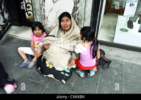 clean indigenous Mexican Indian woman with 2 little girls & a baby sits begging on sidewalk outside hotel in Centro Mexico City Stock Photo
