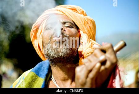 Sadhu smoking marijuana from chilum (clay pipe ) during  the festival at Ridi bazaar ,Nepal - Stock Photo