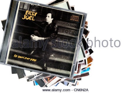 Billy Joel 1983 An Innocent Man album on a stack of CD cases on a white background, England - Stock Photo