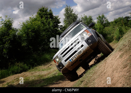 Landrover Discovery drives over difficult, uneven terrain. - Stock Photo